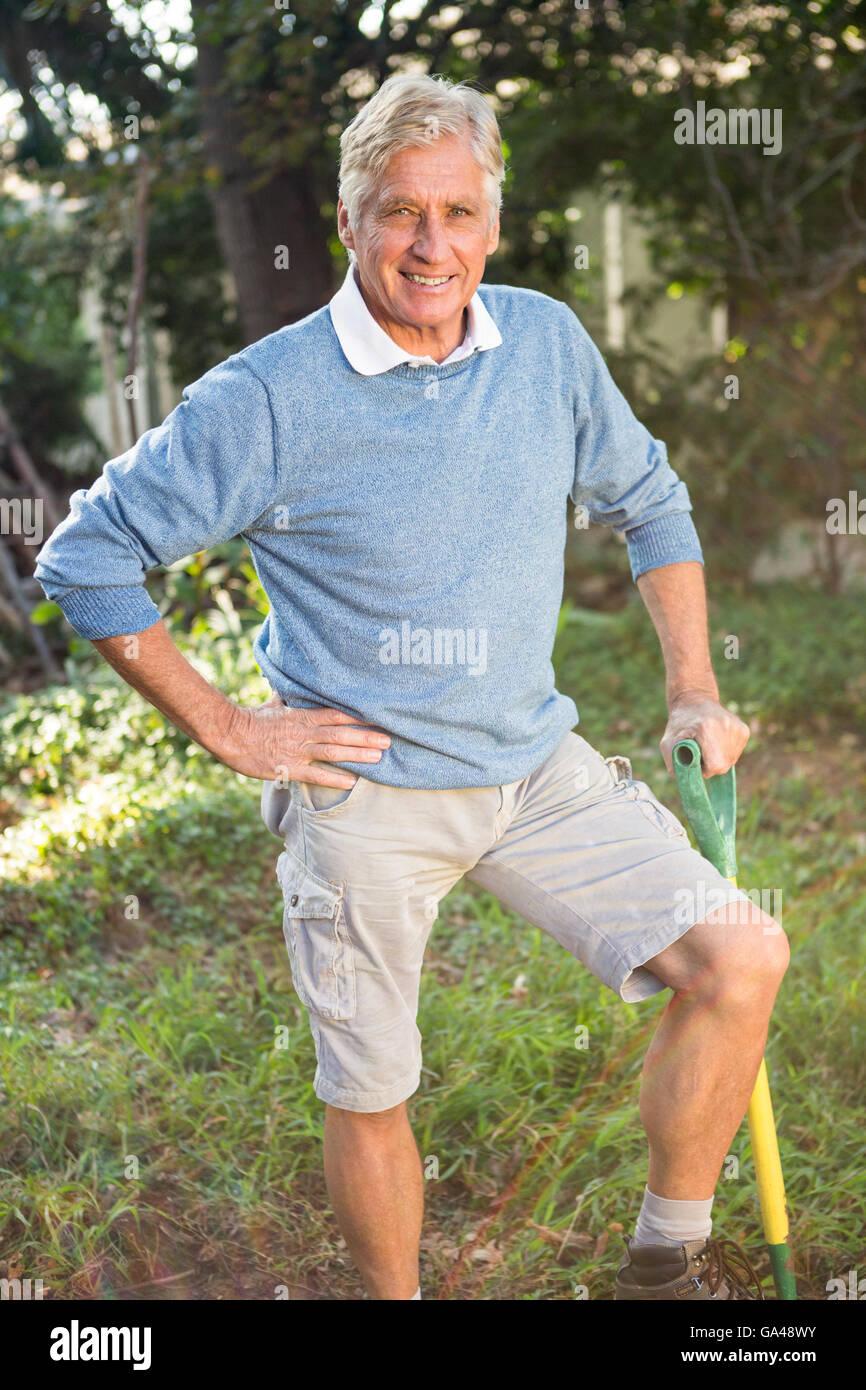Portrait de jardinier heureux avec l'outil debout à jardin Banque D'Images