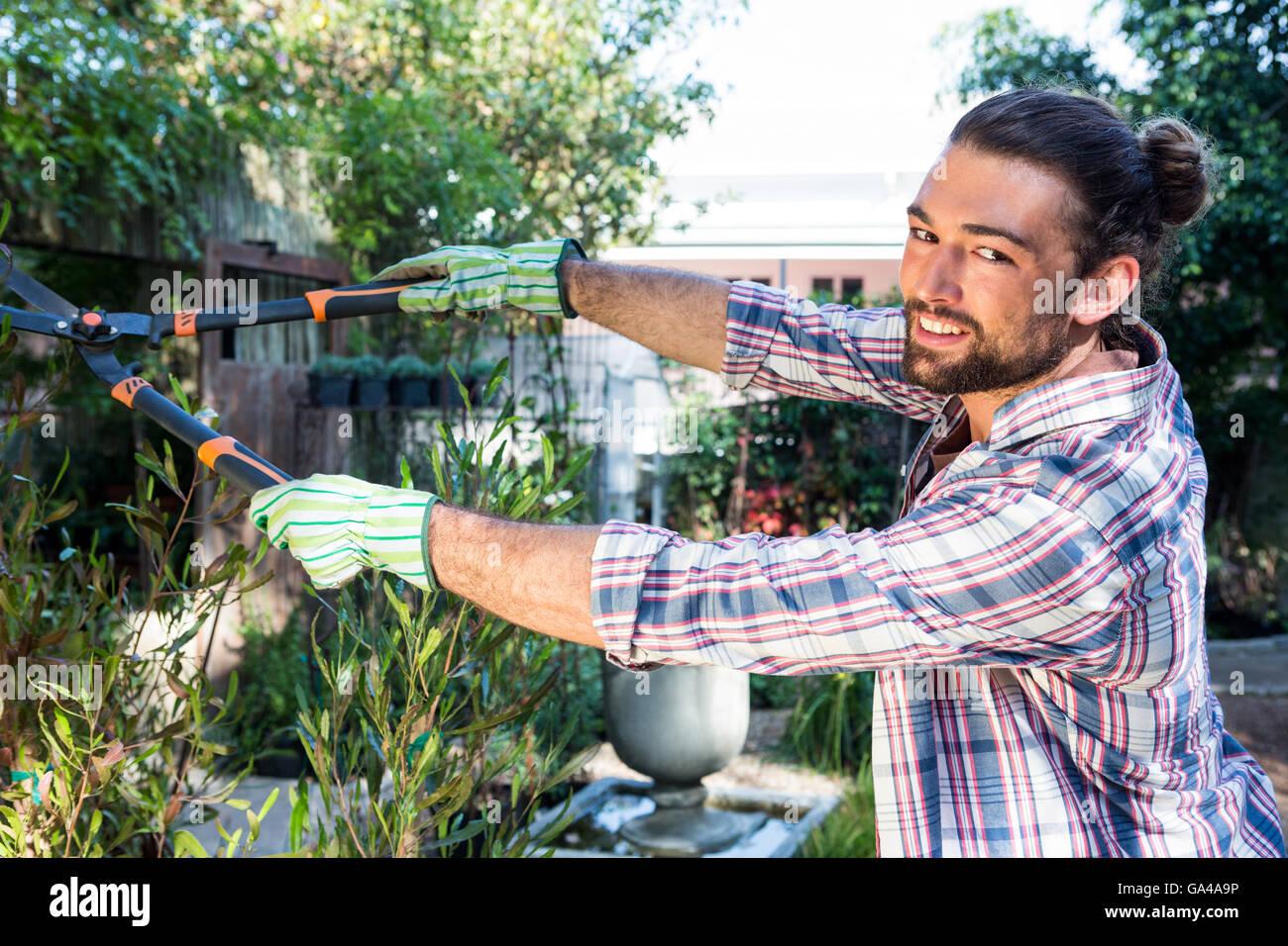 Portrait de l'aide jardinier heureux clippers au jardin Photo Stock