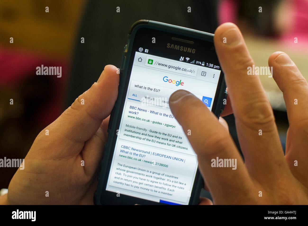 """Un homme types dans google """"Qu'est-ce que l'Union européenne"""" sur son téléphone Photo Stock"""
