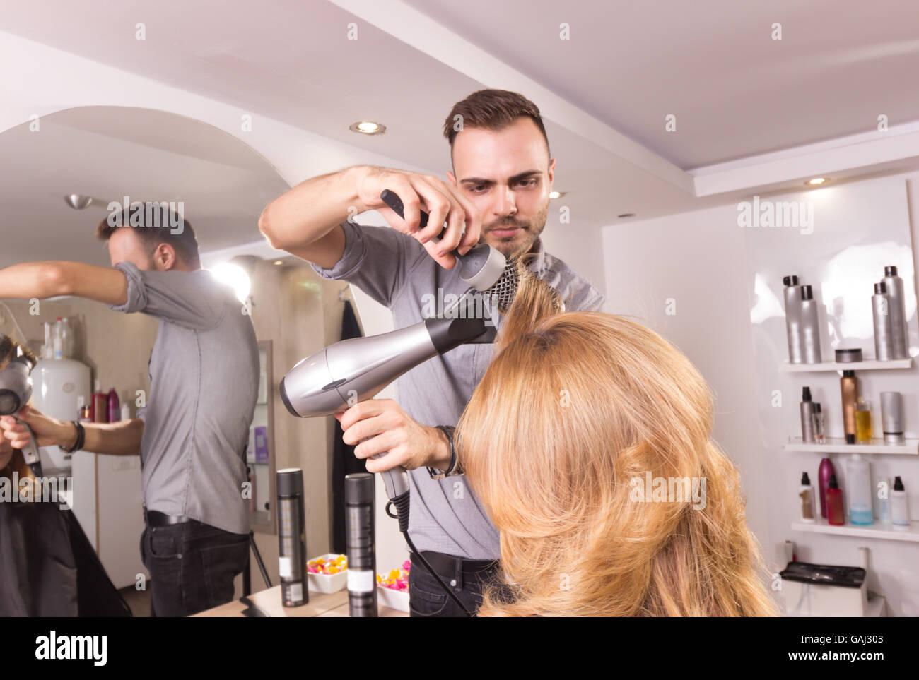 Coup de peigne de coiffeur homme femme rouleau séchage des cheveux, vue latérale Photo Stock