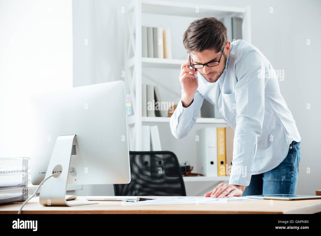 Jeune homme debout à l'entreprise handsoome 24 travaillant sur des documents avec mobile phoone in office Banque D'Images