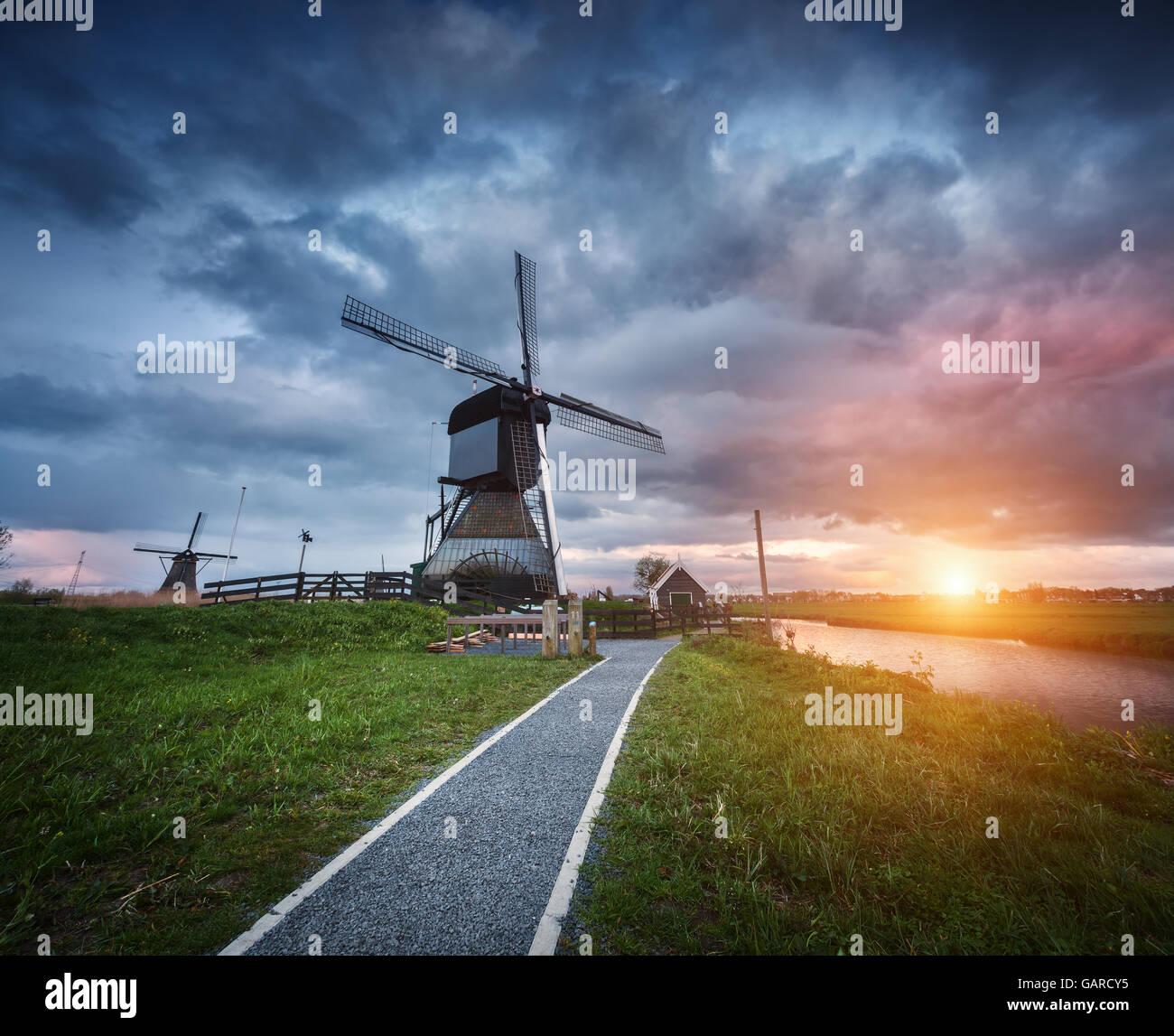 Paysage aux moulins à vent traditionnel néerlandais et le chemin près de l'eau des canaux. Nuages Photo Stock