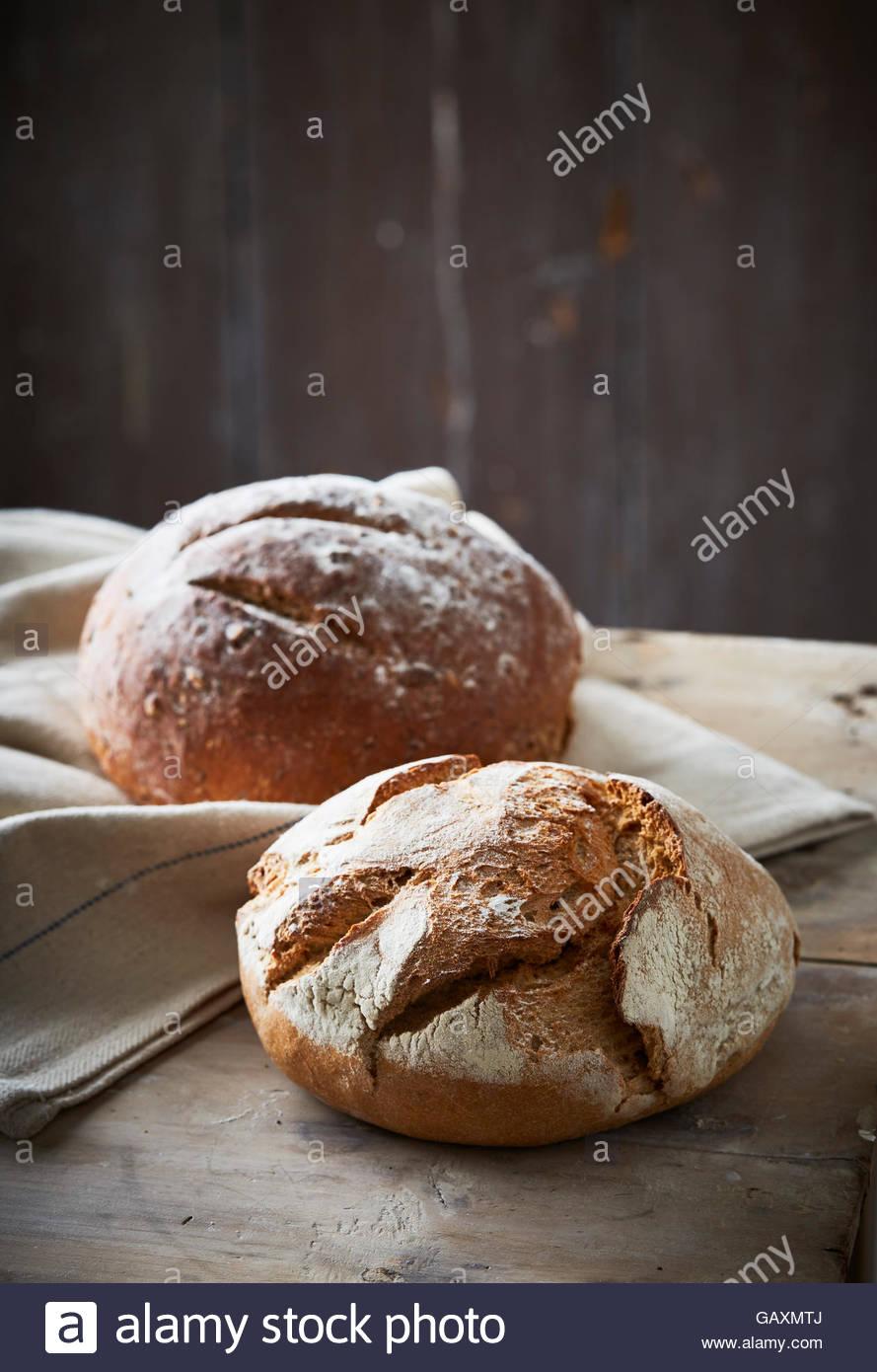 Deux pains de boulangerie artisanale sur fond sombre avec tissu en lin Photo Stock