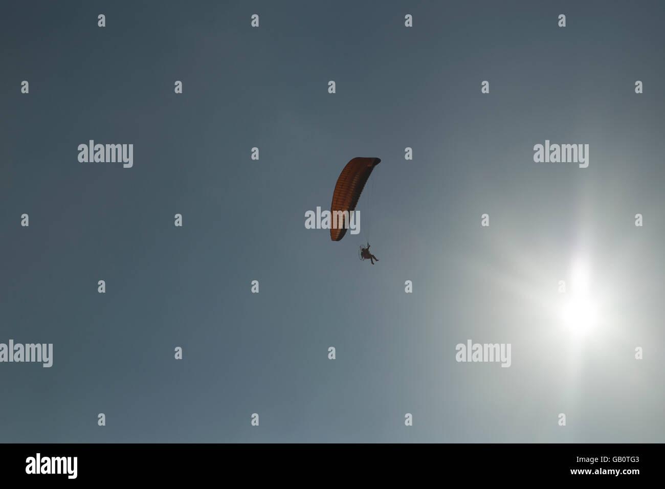 Parapentiste contre le soleil et ciel sans nuages. Photo Stock
