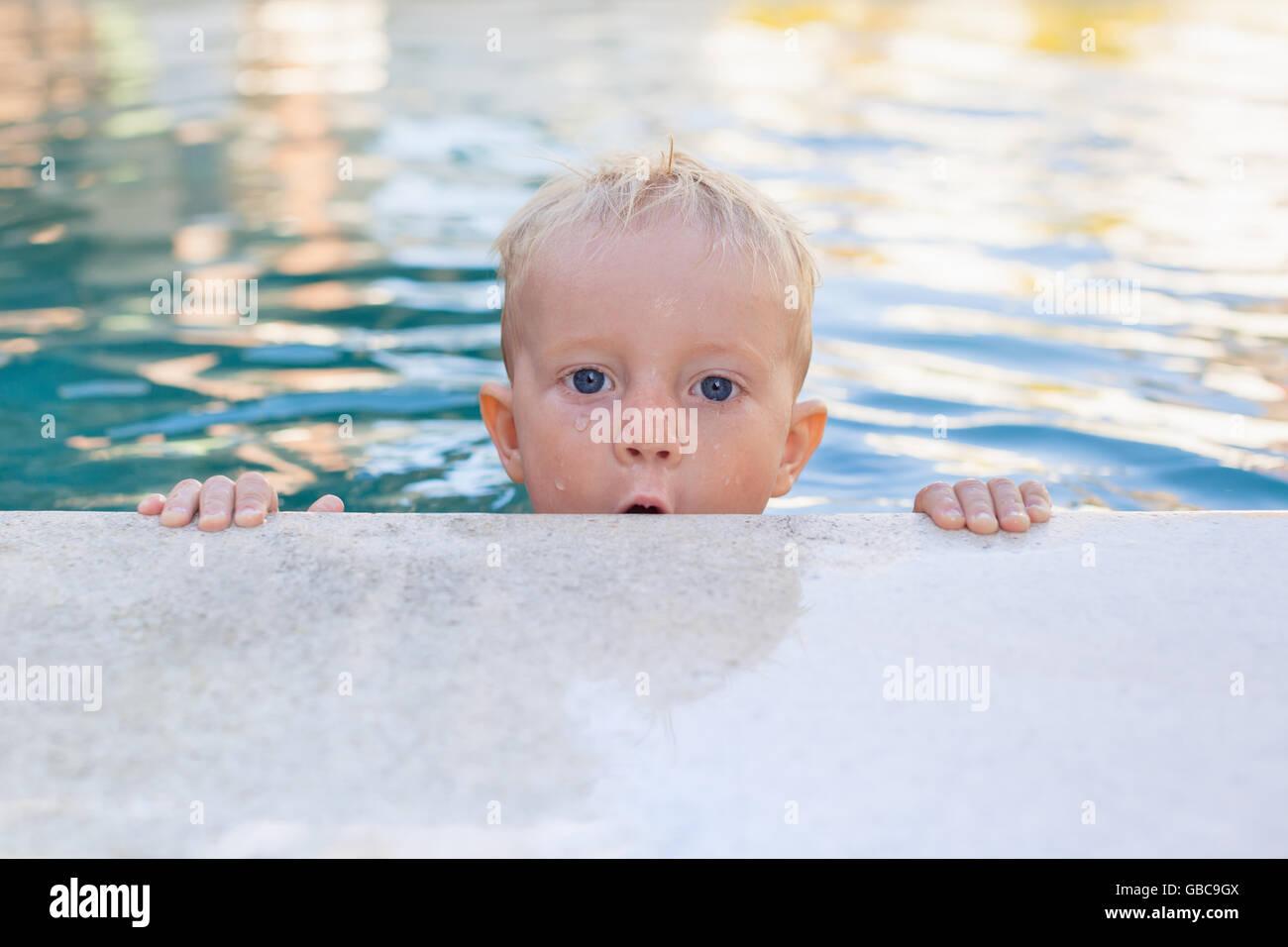 Apprendre à nager - drôle de visage de petit bébé garçon dans la piscine. Vie saine et Photo Stock