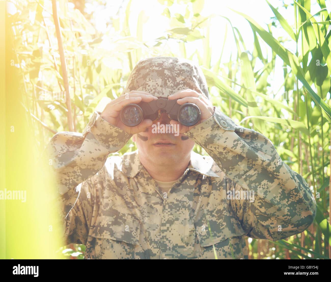 Un soldat l'homme est à la recherche à travers les jumelles dans les bois à l'extérieur avec une protection uniforme sur d'une guerre, ou un chasseur concept. Banque D'Images