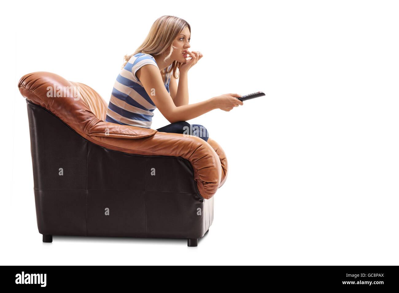Jeune femme regardant la TV et de mordre ses ongles assis sur un fauteuil isolé sur fond blanc Photo Stock
