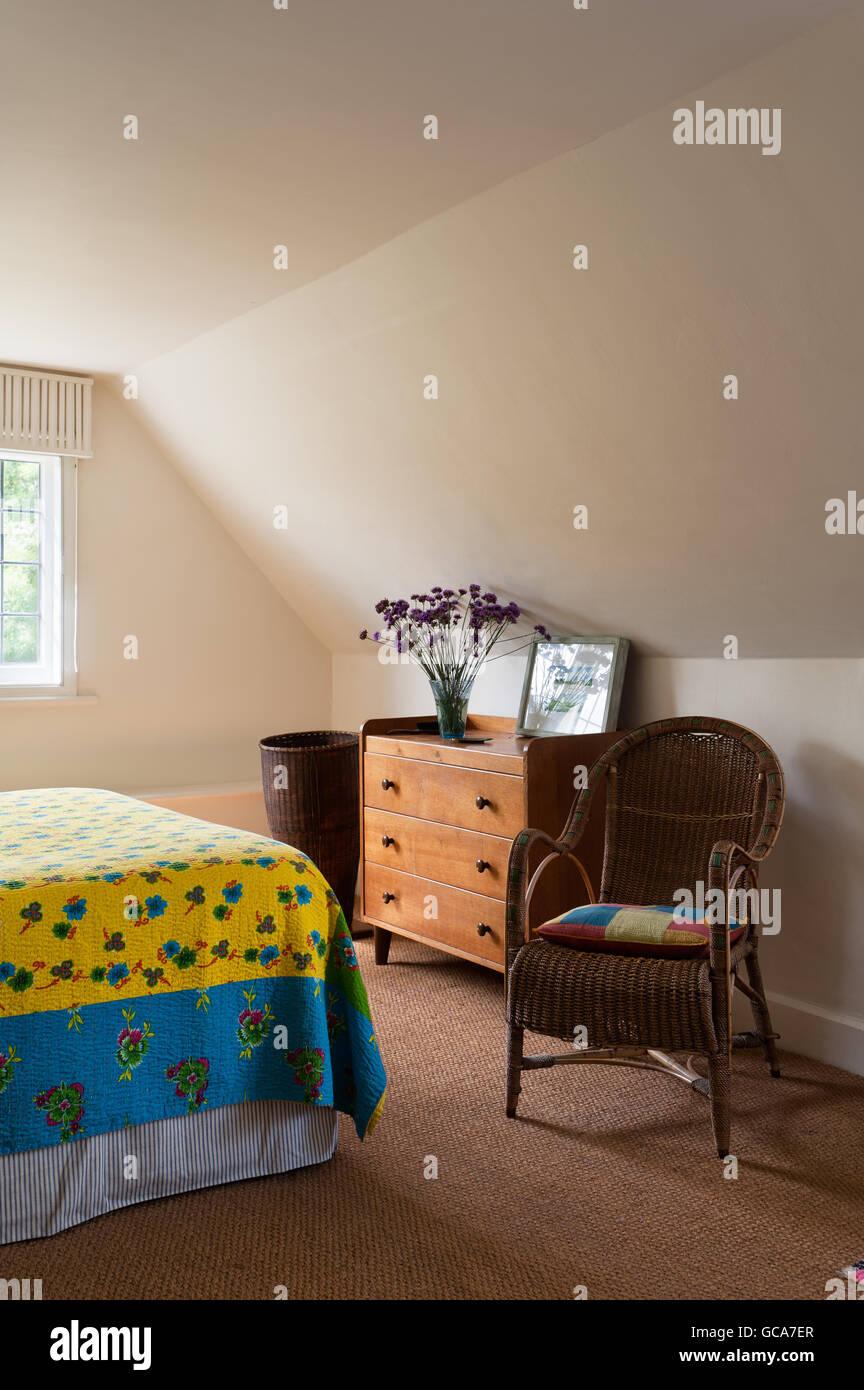 3-tiroir Gordon Russell et poitrine 1920 wicker dans chambre avec courtepointe indienne jaune et de plafonds en Photo Stock