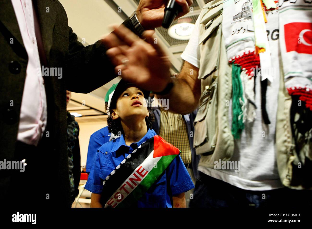Abdul Hamid , neuf ans, regarde son père Al Mahdi Al Harati, parle à la presse à l'aéroport de Dublin. Banque D'Images