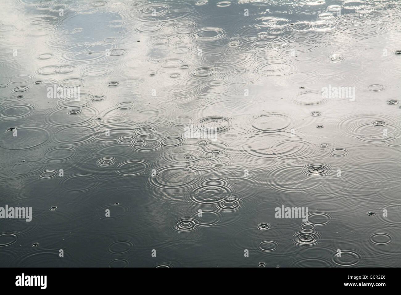 Des gouttelettes de pluie frappant une mer lisse Photo Stock