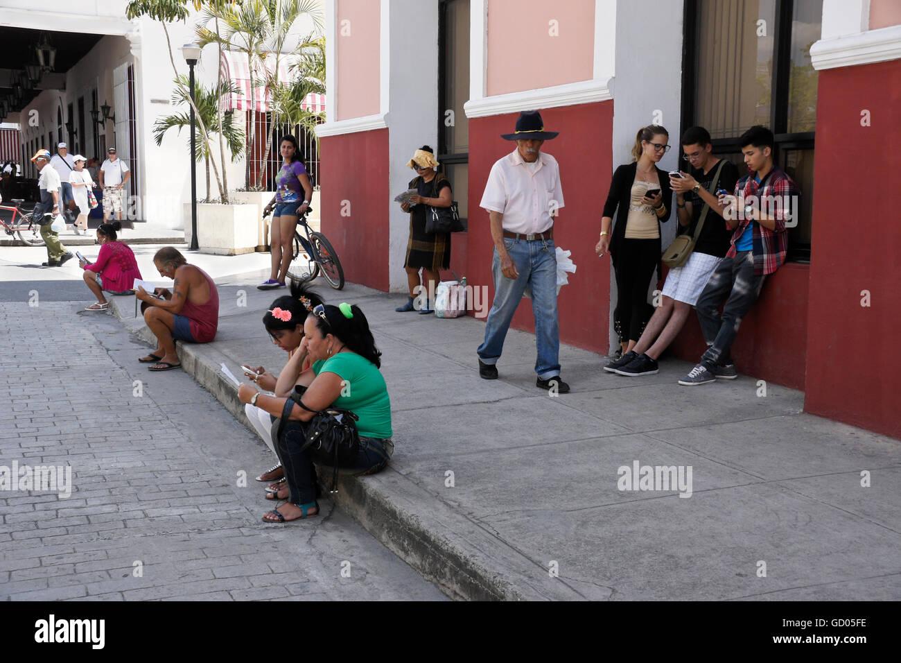 Les gens ramasser signal wi-fi sur les téléphones mobiles, rue piétonne, près de la Plaza de Photo Stock