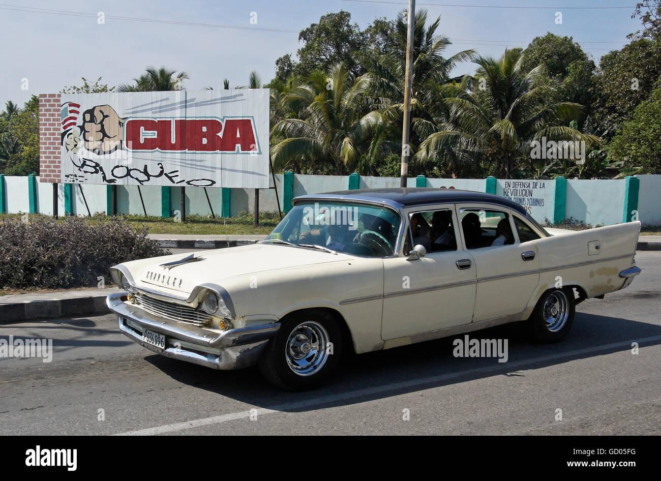 Vieux taxi Chrysler passe un panneau pour protester contre l'embargo américain, La Havane, Cuba Photo Stock