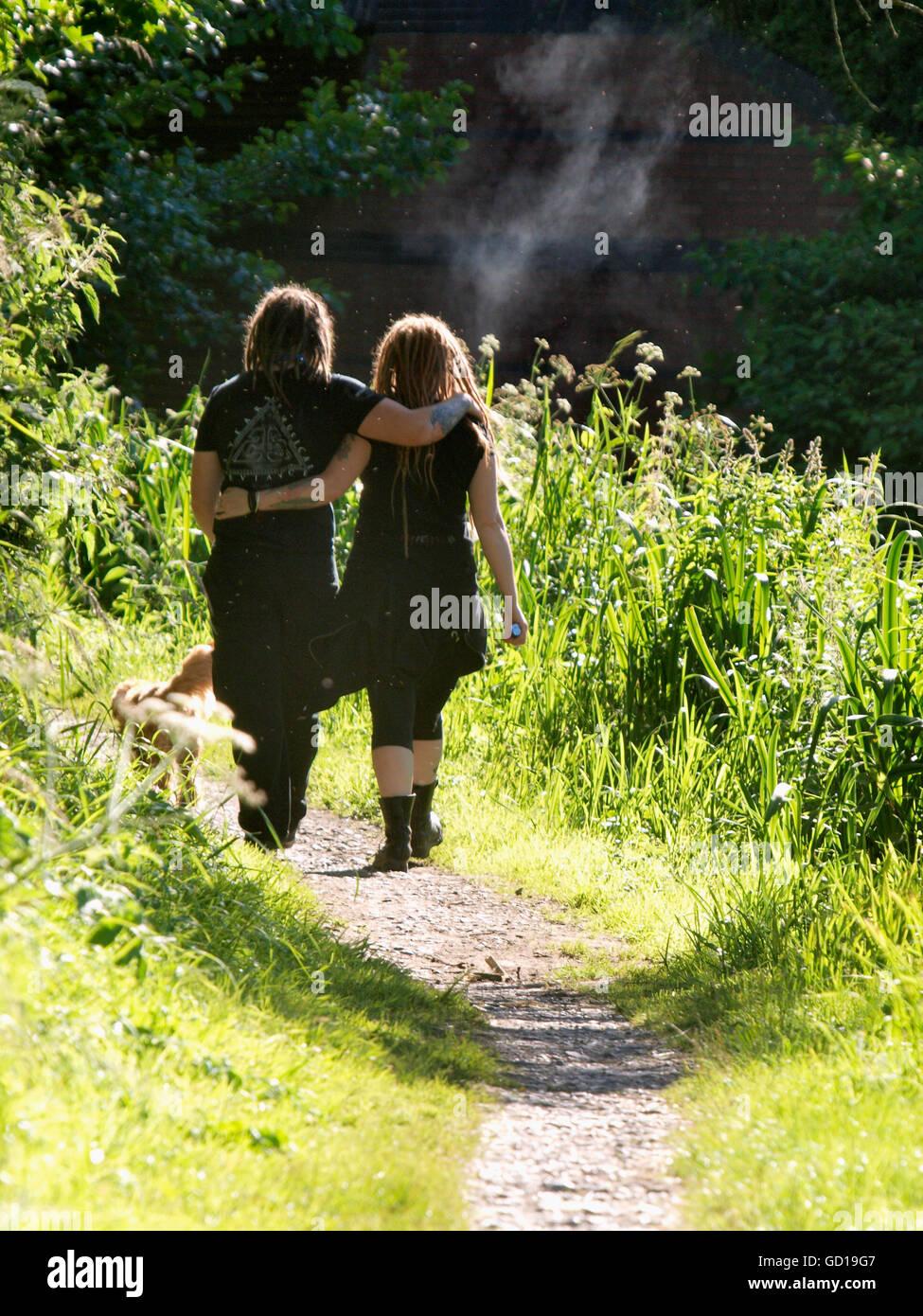 Jeune couple en train de marcher le long d'un sentier, l'autre ronde d'armes dans le soleil d'été, Photo Stock