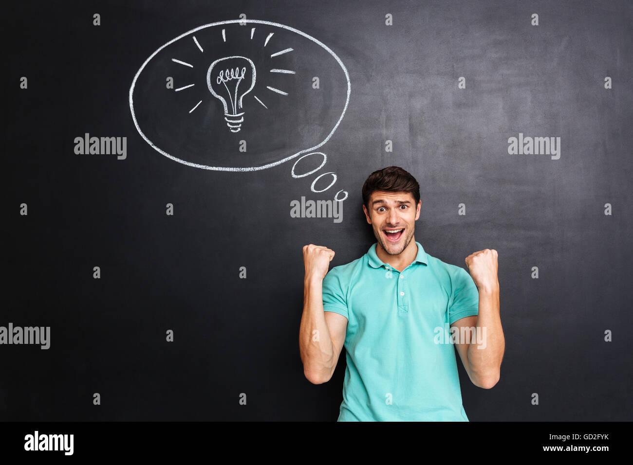 Succès joyeux jeune homme ayant une idée et célébrons les succès sur fond de tableau noir Photo Stock