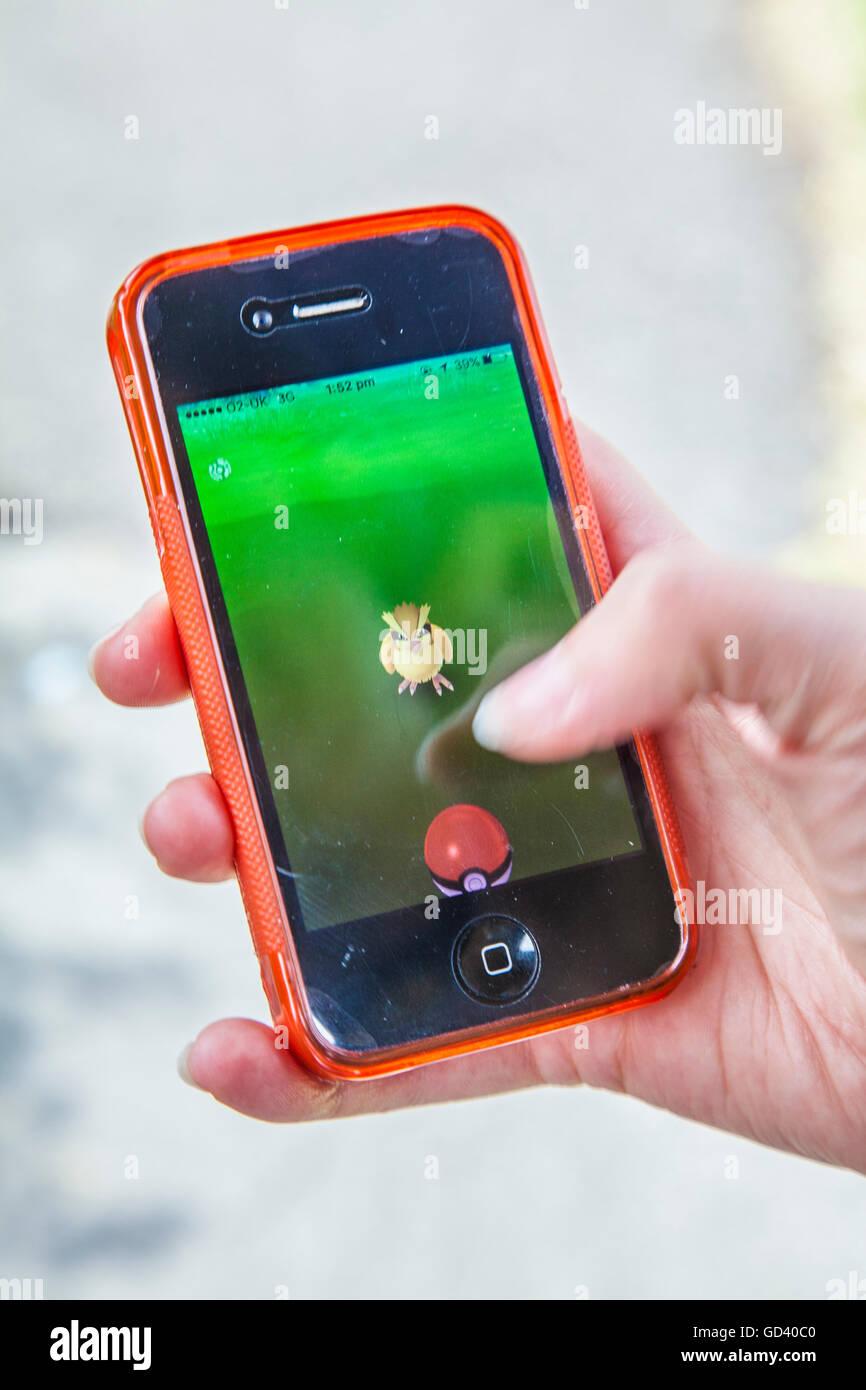 Une jeune personne utilise un iPhone pour jouer à Pokémon sur rendez-vous, le dernier jeu de réalité Photo Stock