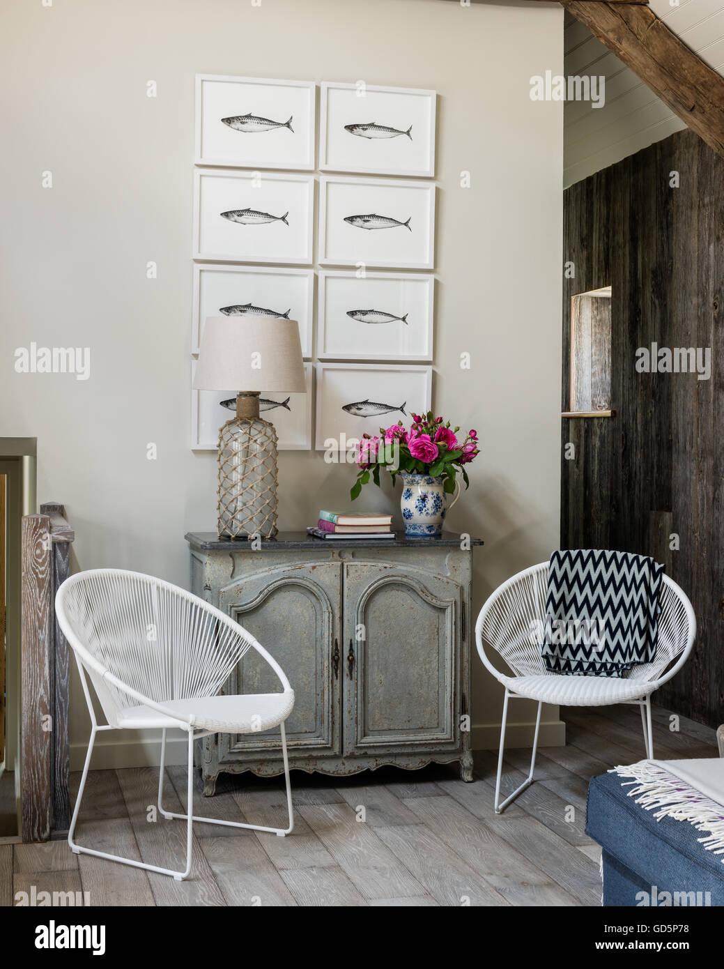 Plume et encre, dessins de maquereau par Kate Stein sur mur de cottage salon avec toit en pente. Les chaises blanches Photo Stock