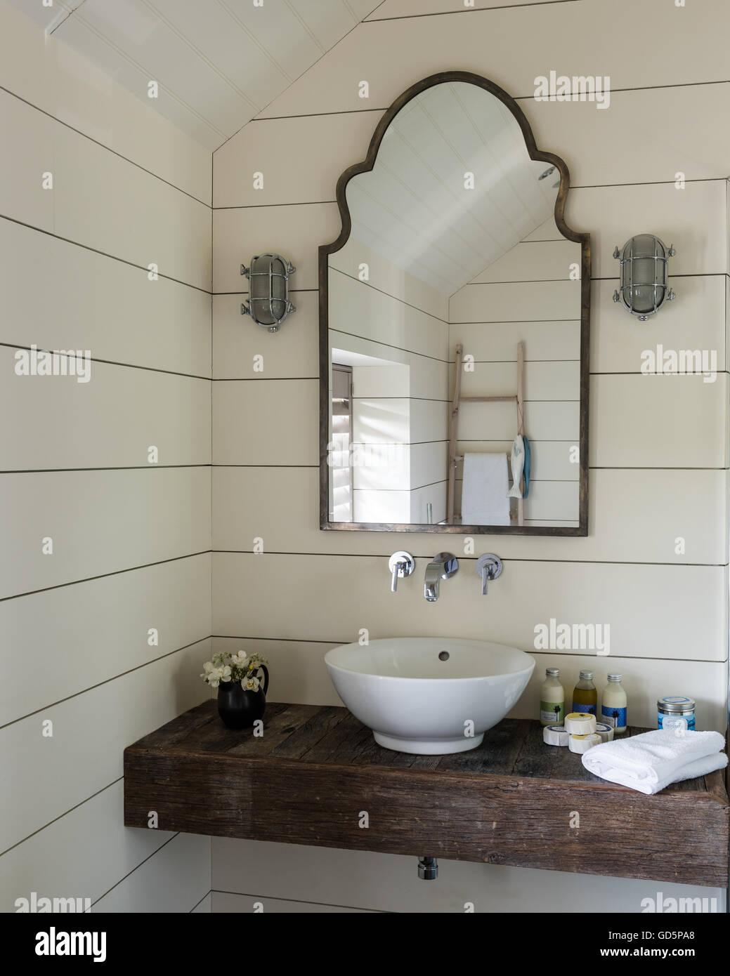 le lavabo de salle de bains en bois dalle avec des murs peints en blanc et les conseils dun miroir vintage