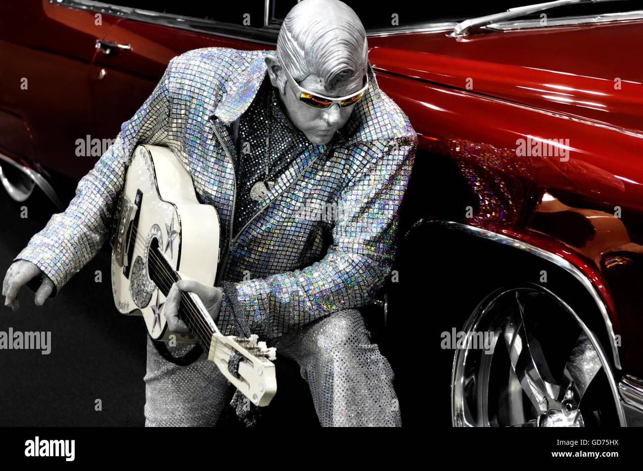 Elvis d'argent avec une guitare à genoux près d'une voiture classique rouge, d'interprètes Photo Stock