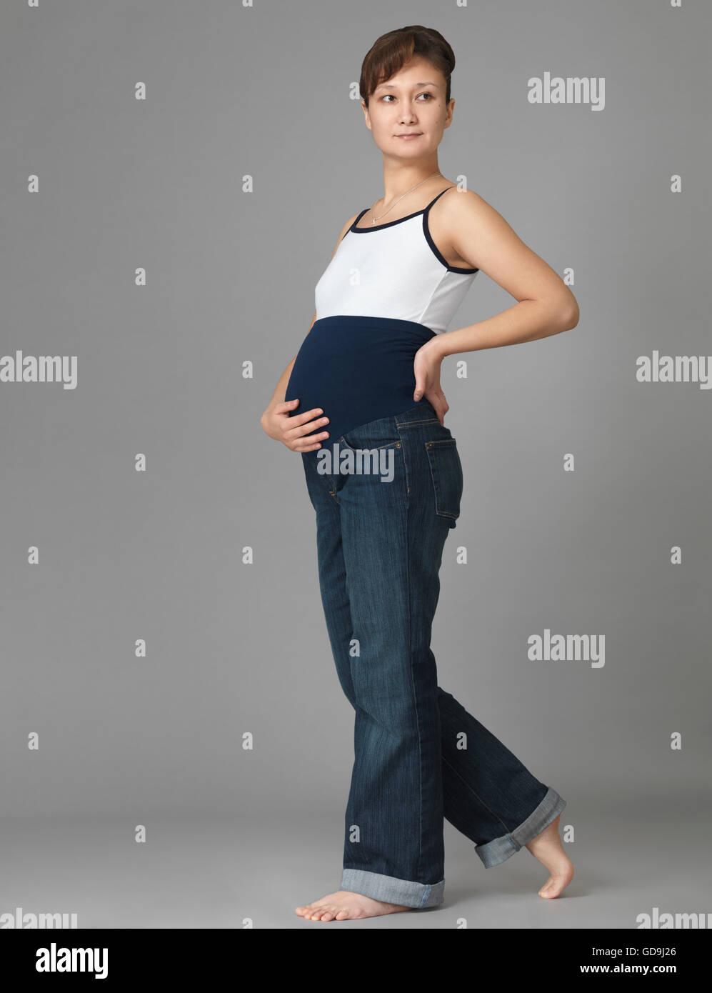 Jeune femme enceinte portant des jeans de maternité avec une bande élastique autour de son ventre Photo Stock