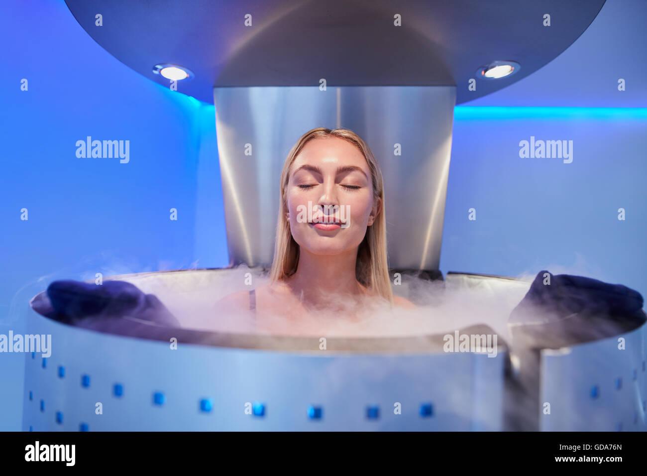 Portrait de jeune femme dans une cabine avec la cryothérapie corps entier les yeux fermés. Cryosauna chambre Photo Stock