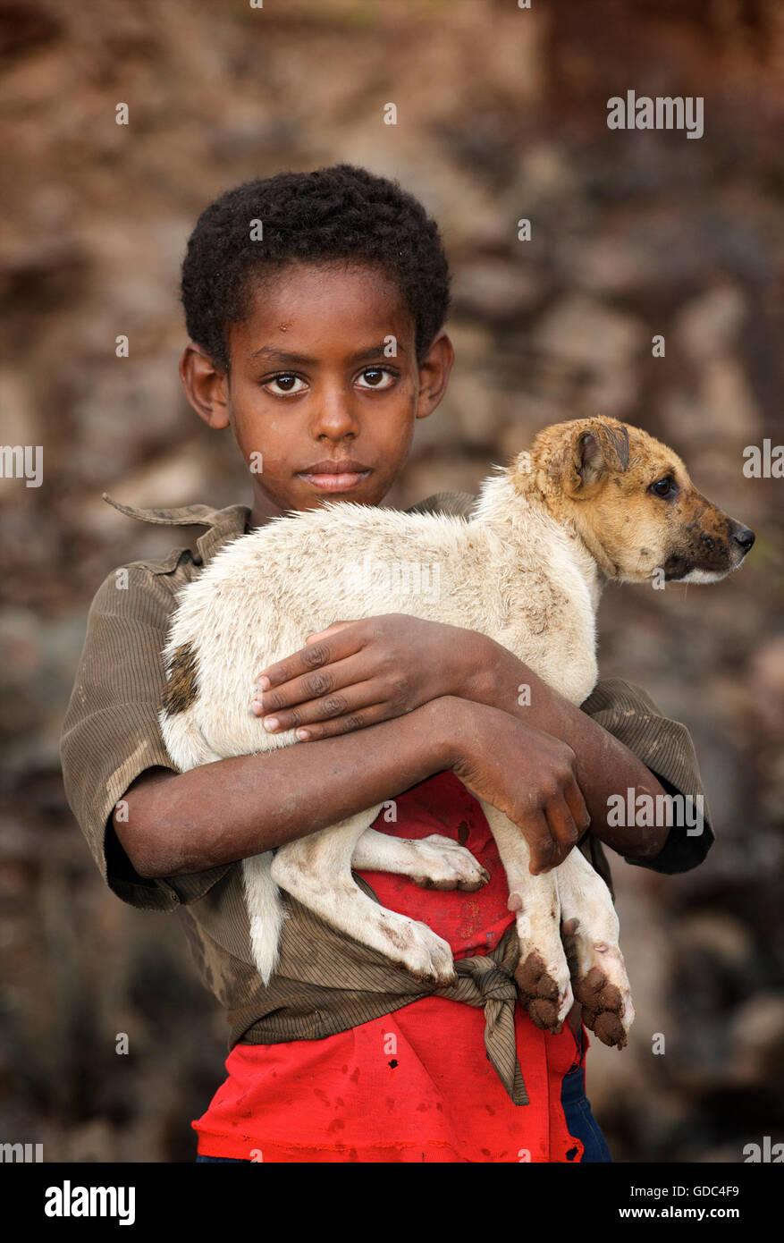 Boy holding éthiopien chien timide. La route d'écorcer, Éthiopie. Photo Stock