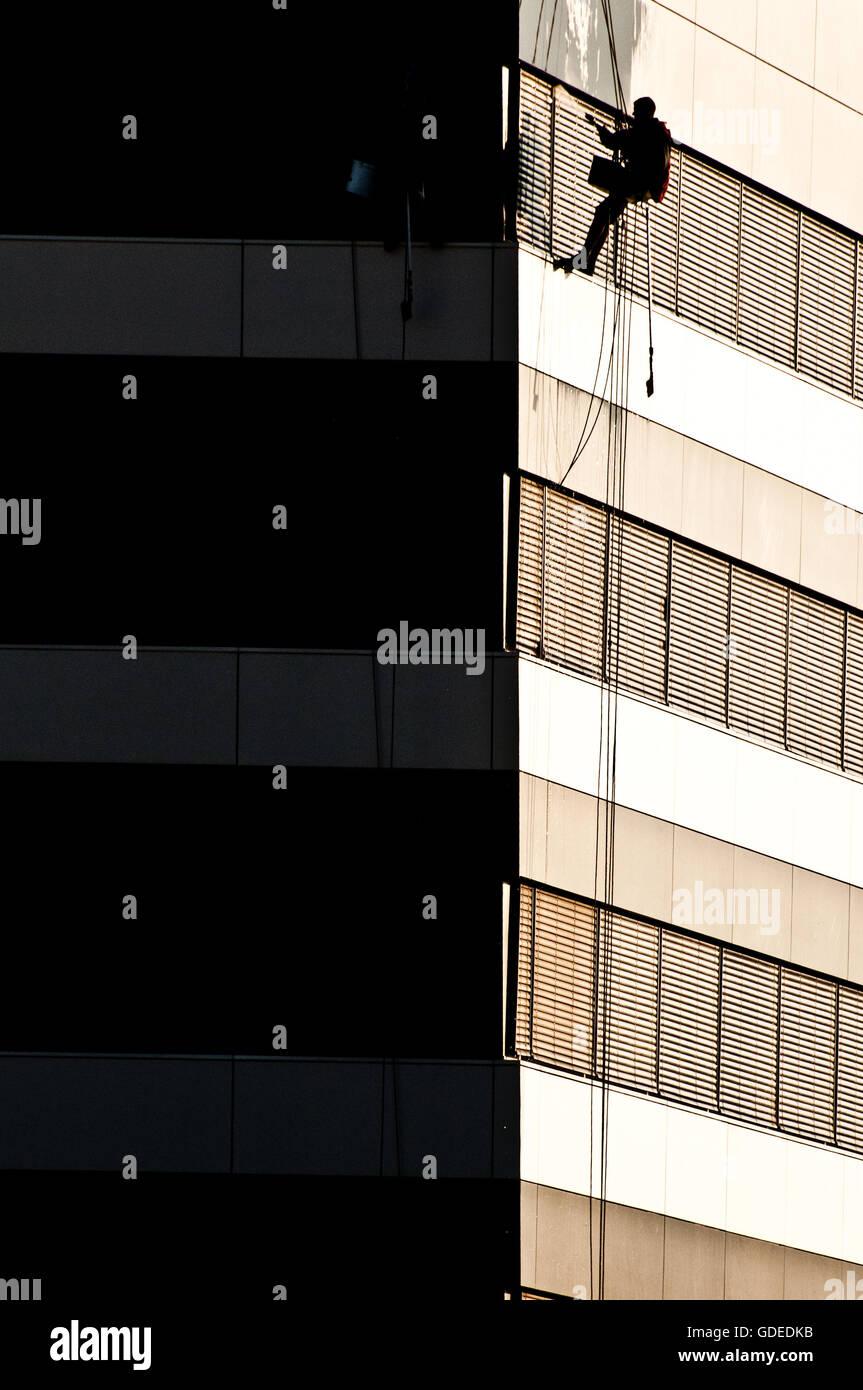 Nettoyant vitres d'un bâtiment moderne sur corde Photo Stock