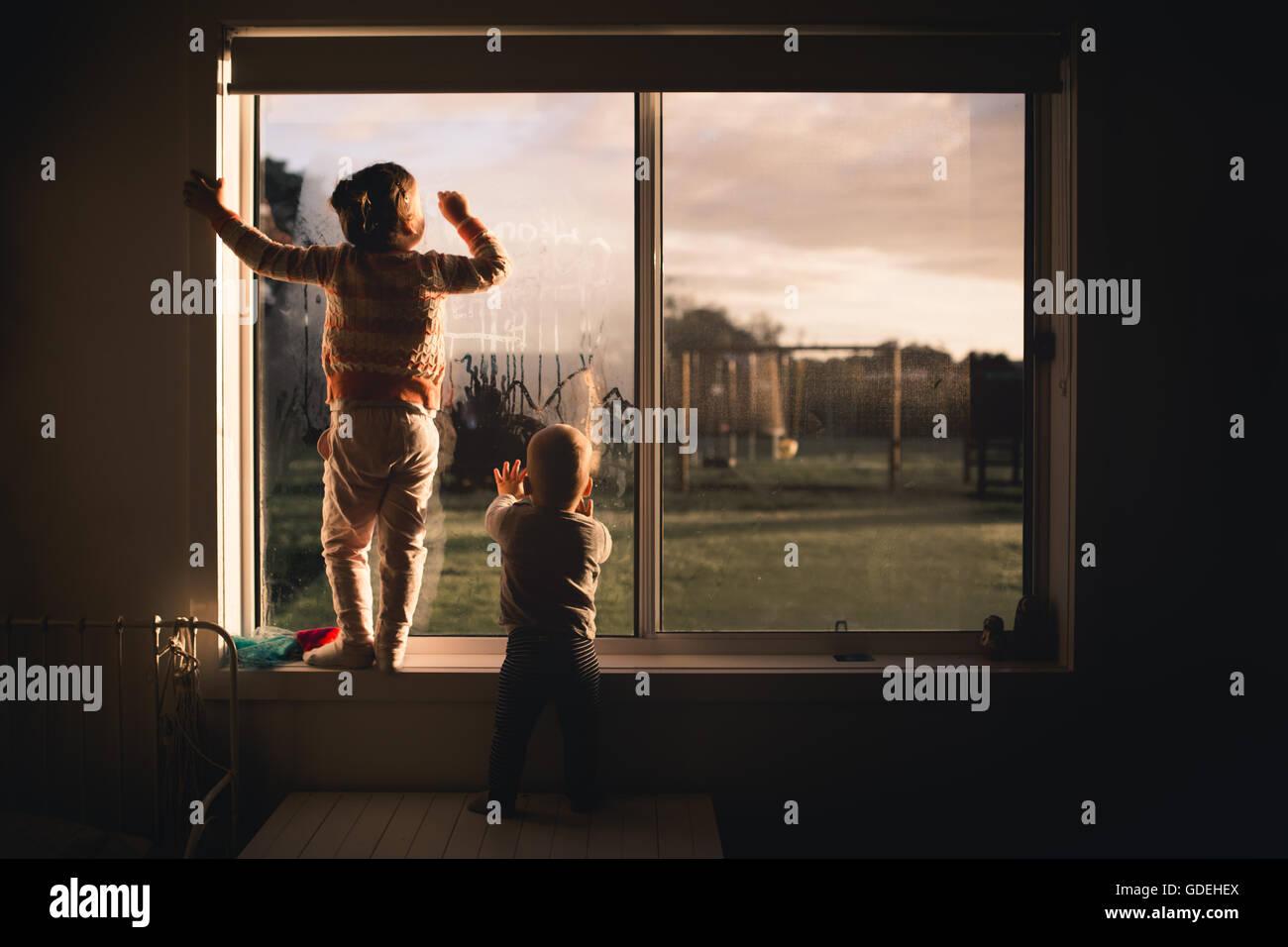 Garçon et fille s'appuyant sur la fenêtre dans la condensation du matin Photo Stock