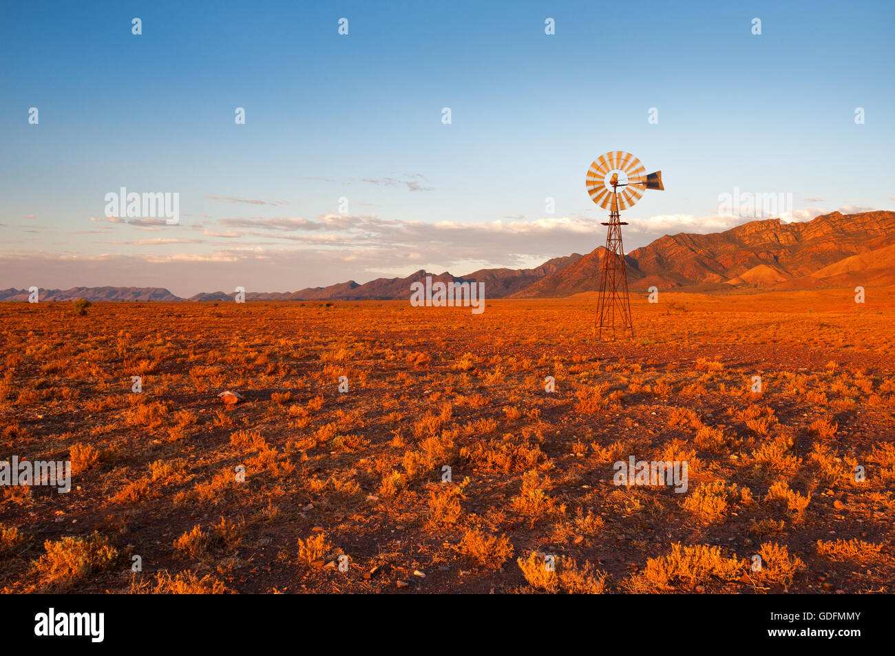 Australie - Moulin typique dans la teinte rouge d'un coucher de soleil. Photo Stock