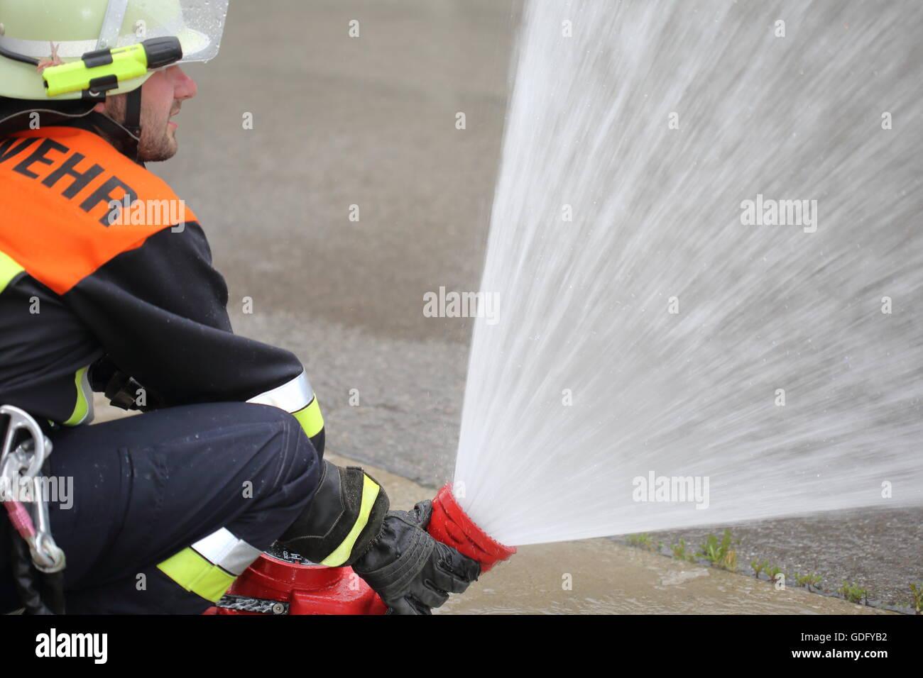Un pompier avec lance de pulvérisation de canon à eau moniteur Photo Stock