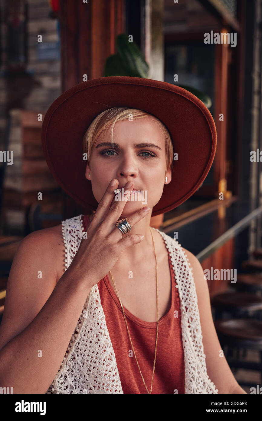 Portrait of young woman with hat fumer une cigarette dans un café. Photo Stock