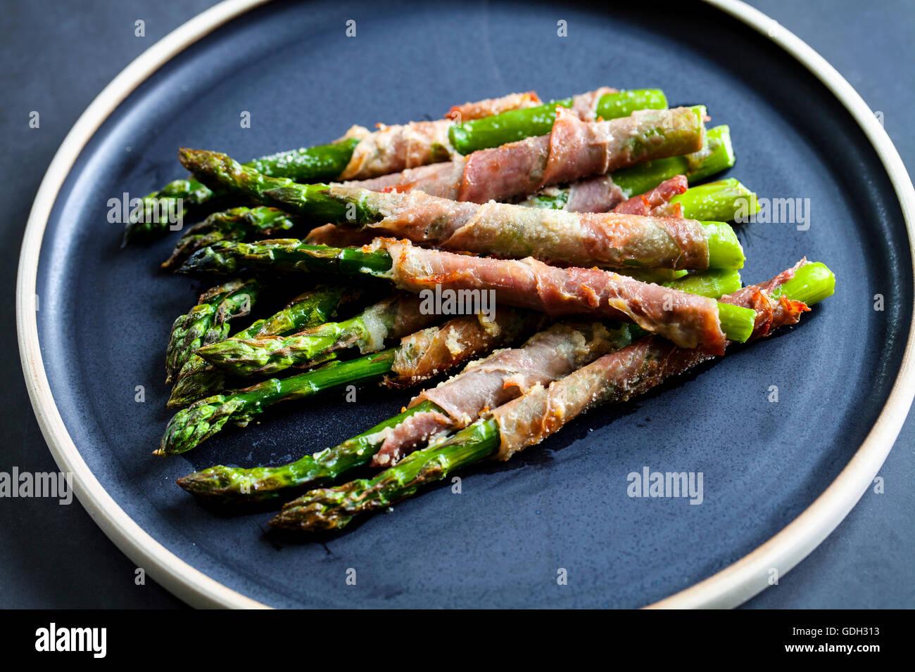Asperges grillées enveloppé dans du jambon de Parme avec sauge et thym Photo Stock