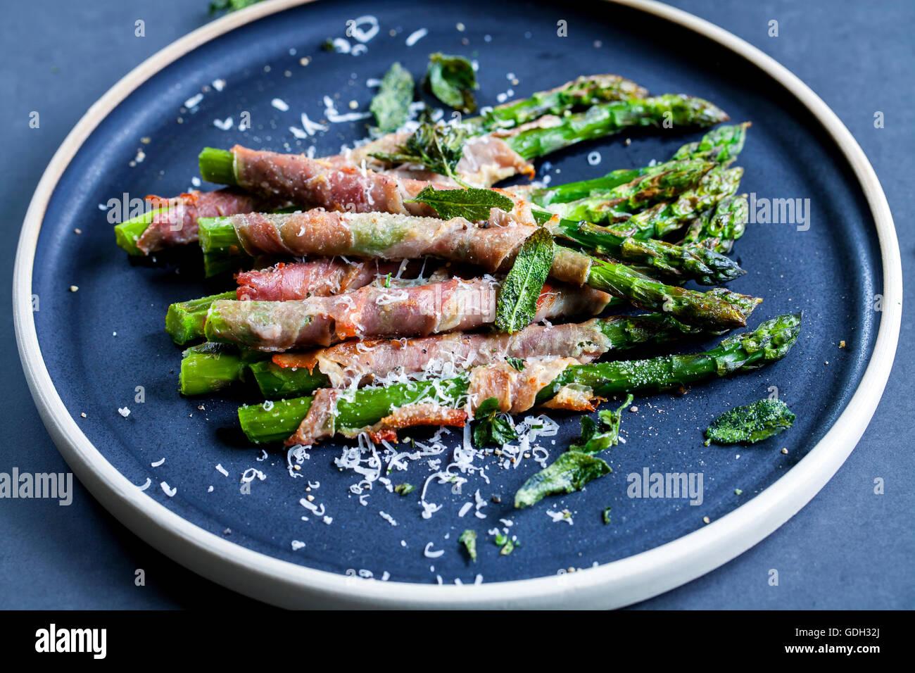 Asperges grillées enveloppé dans du jambon de Parme avec du parmesan, sauge et thym Photo Stock