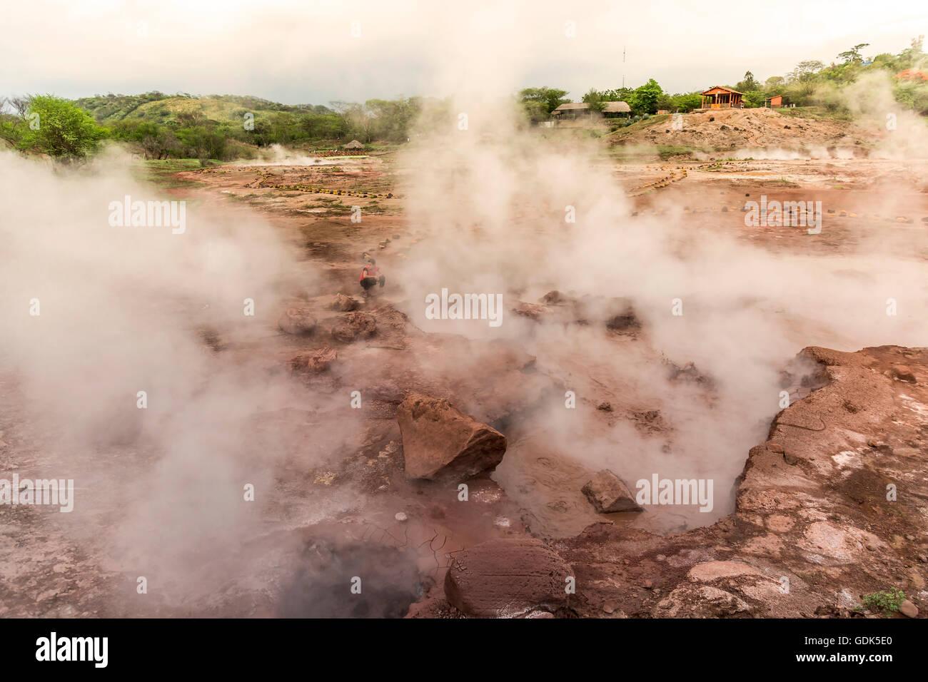 San Jacinto, le Nicaragua - juin 2016. Une fille coin au milieu de piscines de boue bouillante dans un parc volcanique Photo Stock