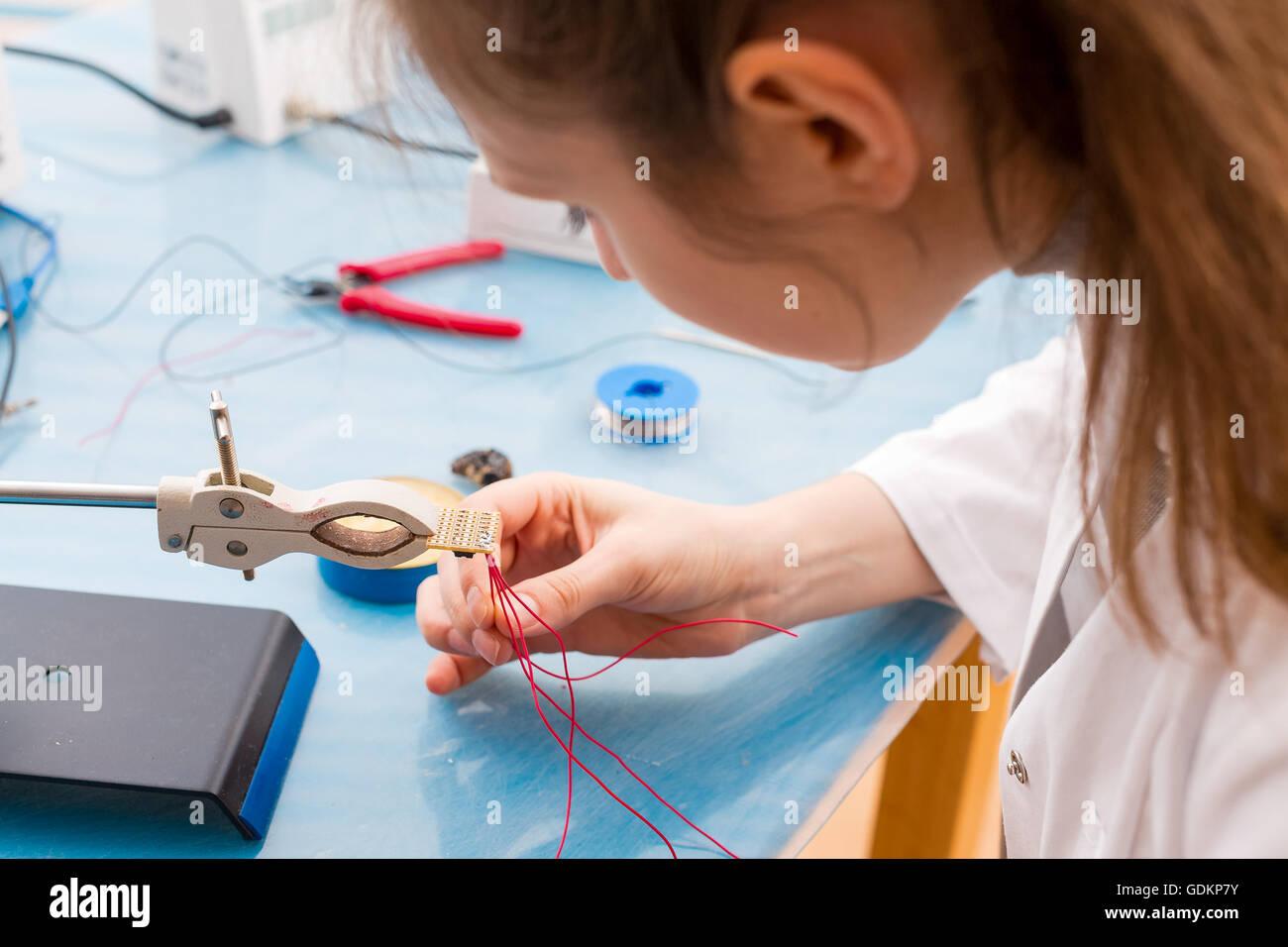 Jeune femme assembler le capteur optique pour le meilleur système de robot Photo Stock