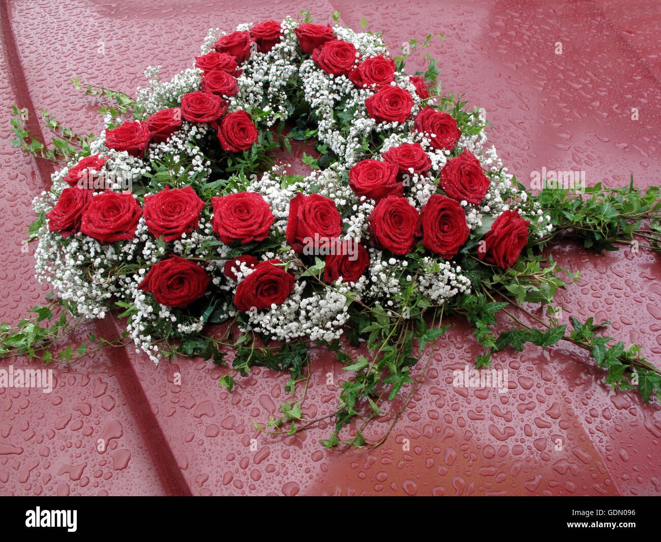 bouquet de fleurs en forme de coeur sur une voiture sous la pluie, l