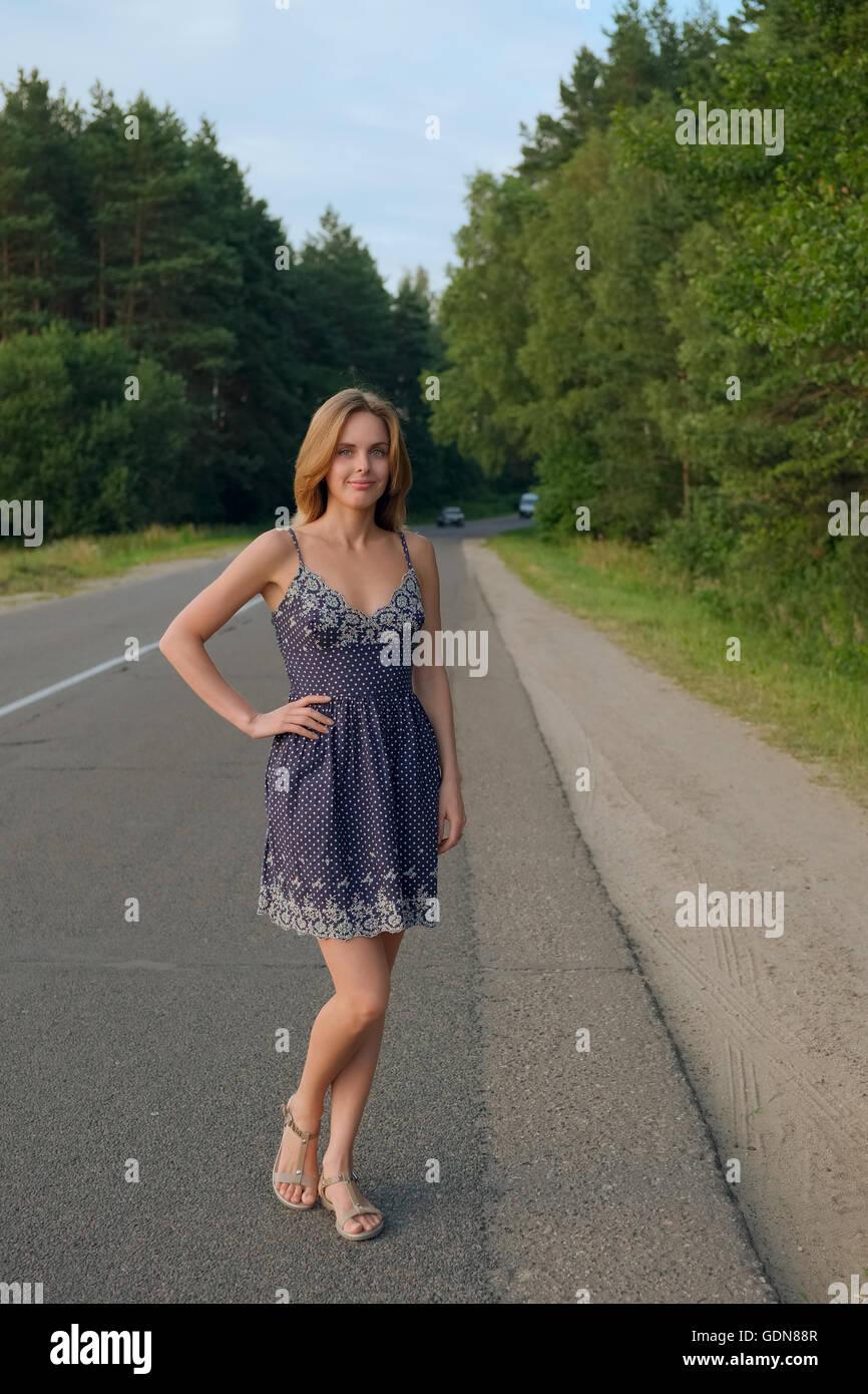 Jolie fille en robe courte sur la route Photo Stock