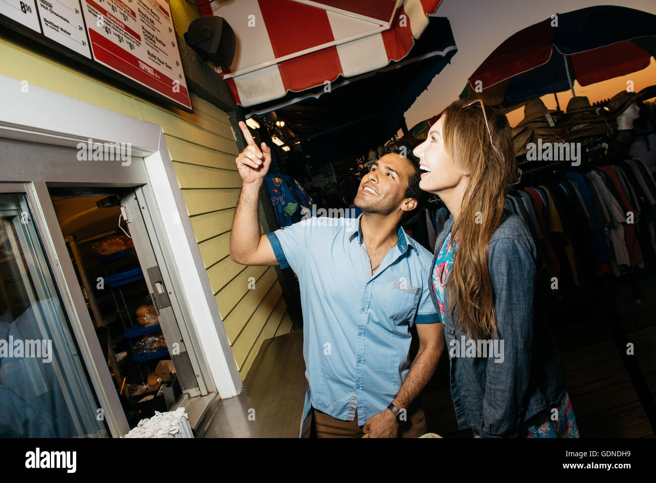 Jeune couple pointing at hotdog menu dans un parc d'attractions de nuit, Santa Monica, Californie, USA Photo Stock