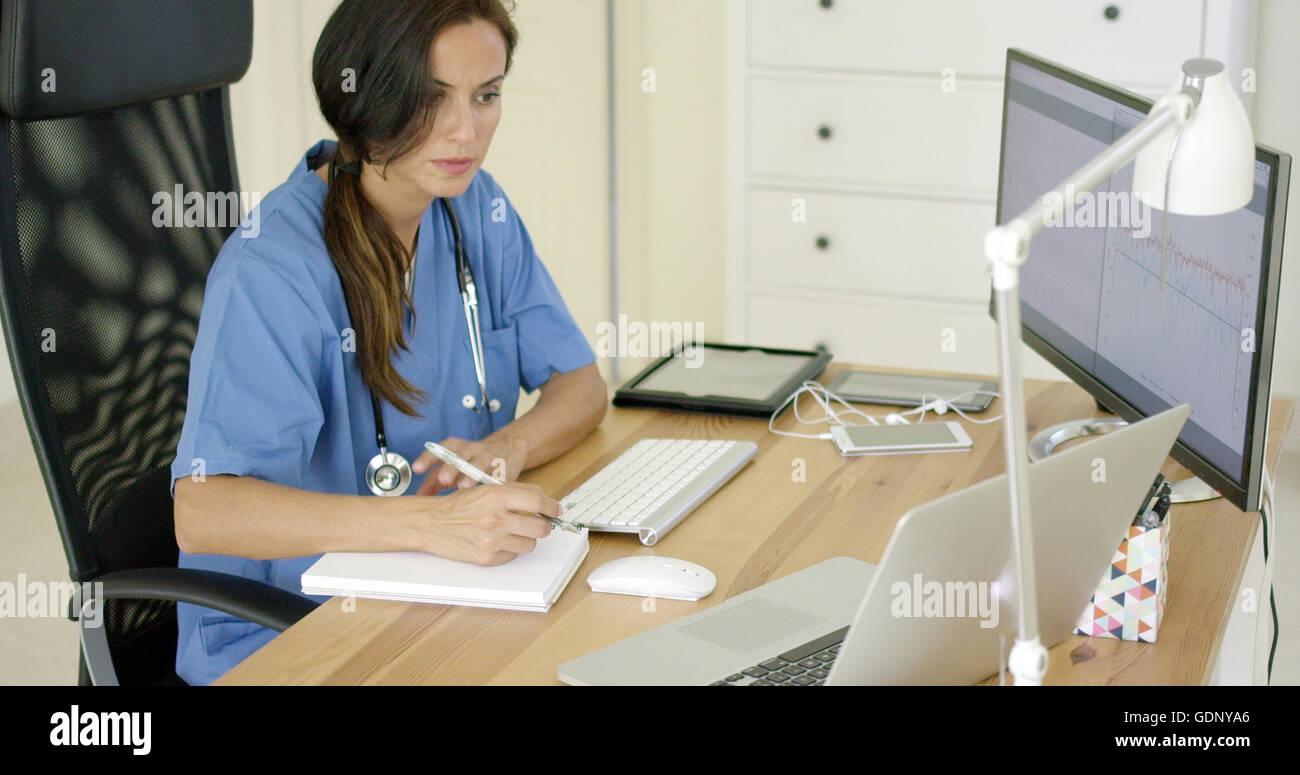 Un médecin travaillant à son bureau dans le bureau Photo Stock