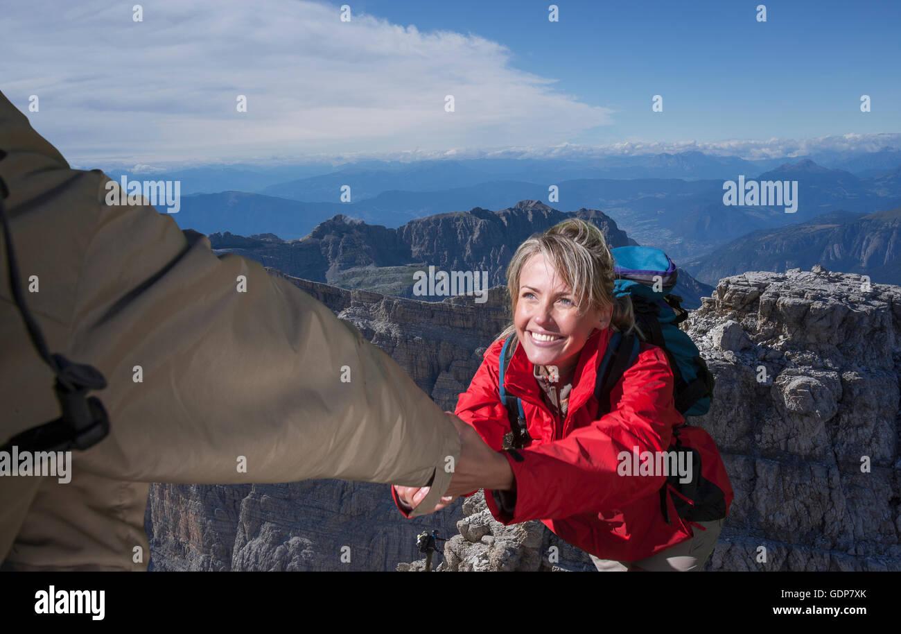 Un grimpeur mâle aider sa partenaire féminine pour atteindre le sommet d'une montagne, Dolomites, Italie Banque D'Images