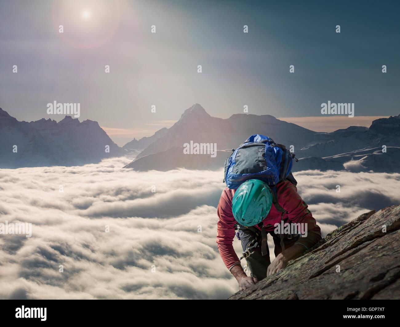 Grimpeur sur un mur rocheux au-dessus d'une mer de brume dans une vallée alpine, Alpes, Canton du Valais, Photo Stock