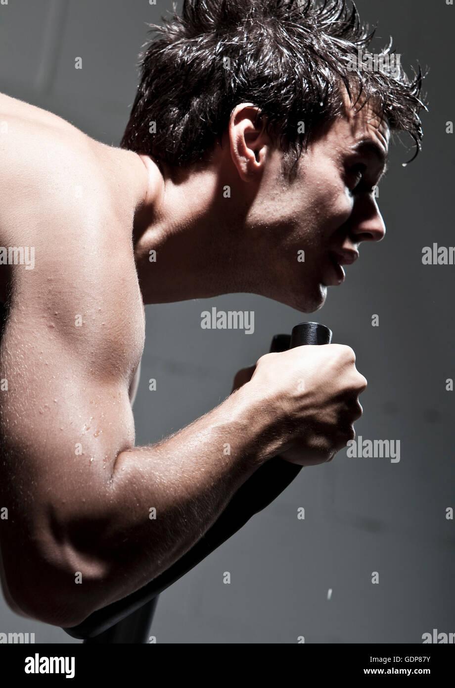 Vue de côté de l'homme à l'aide de machine d'exercice Photo Stock