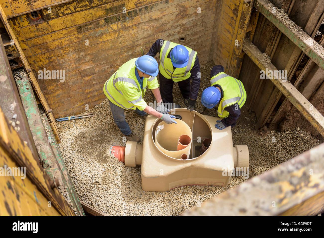 Les constructeurs de l'apprenti dans le trou de drainage avec formation sur site de construction Photo Stock