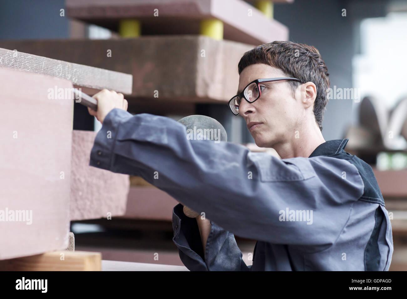 Tailleur de pierre à l'aide de ciseau et maillet sur bloc de pierre Photo Stock