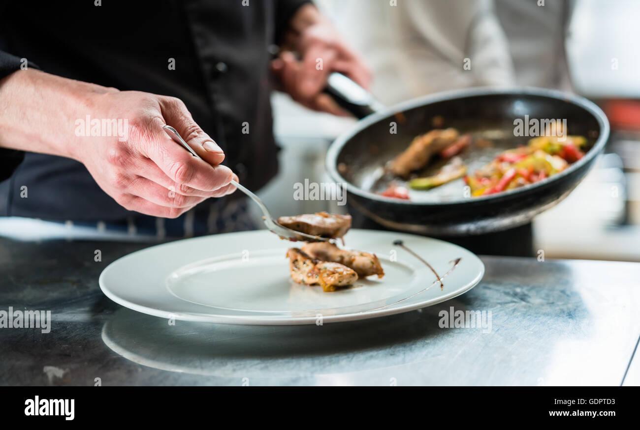 Chef finishing nourriture sur plaque dans restaurant ou cuisine de l'hôtel Banque D'Images