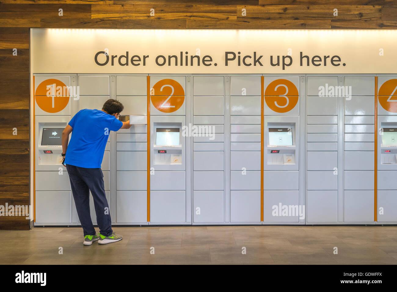 L'homme d'atteindre dans un casier d'ecommerce d'obtenir un paquet qu'il commandé en ligne Photo Stock