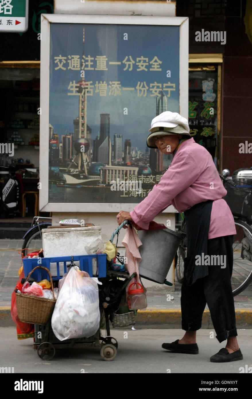 Une femme chinoise pousse un panier avec des choses qu'elle a recueillies sur une rue promenades Banque D'Images