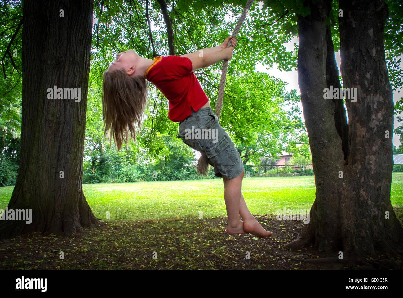Une jeune fille se balançant sur une corde de l'arbre. Photo Stock
