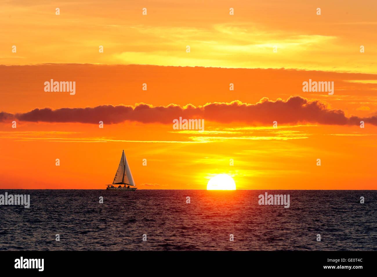 Bateau à coucher du soleil est un voilier se déplaçant le long de l'eau comme le soleil descend Photo Stock