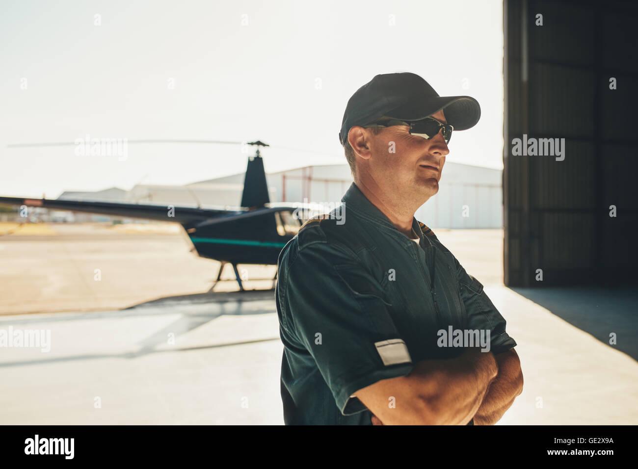 Portrait du pilote de l'hélicoptère en uniforme debout avec les bras croisés et à la voiture Photo Stock