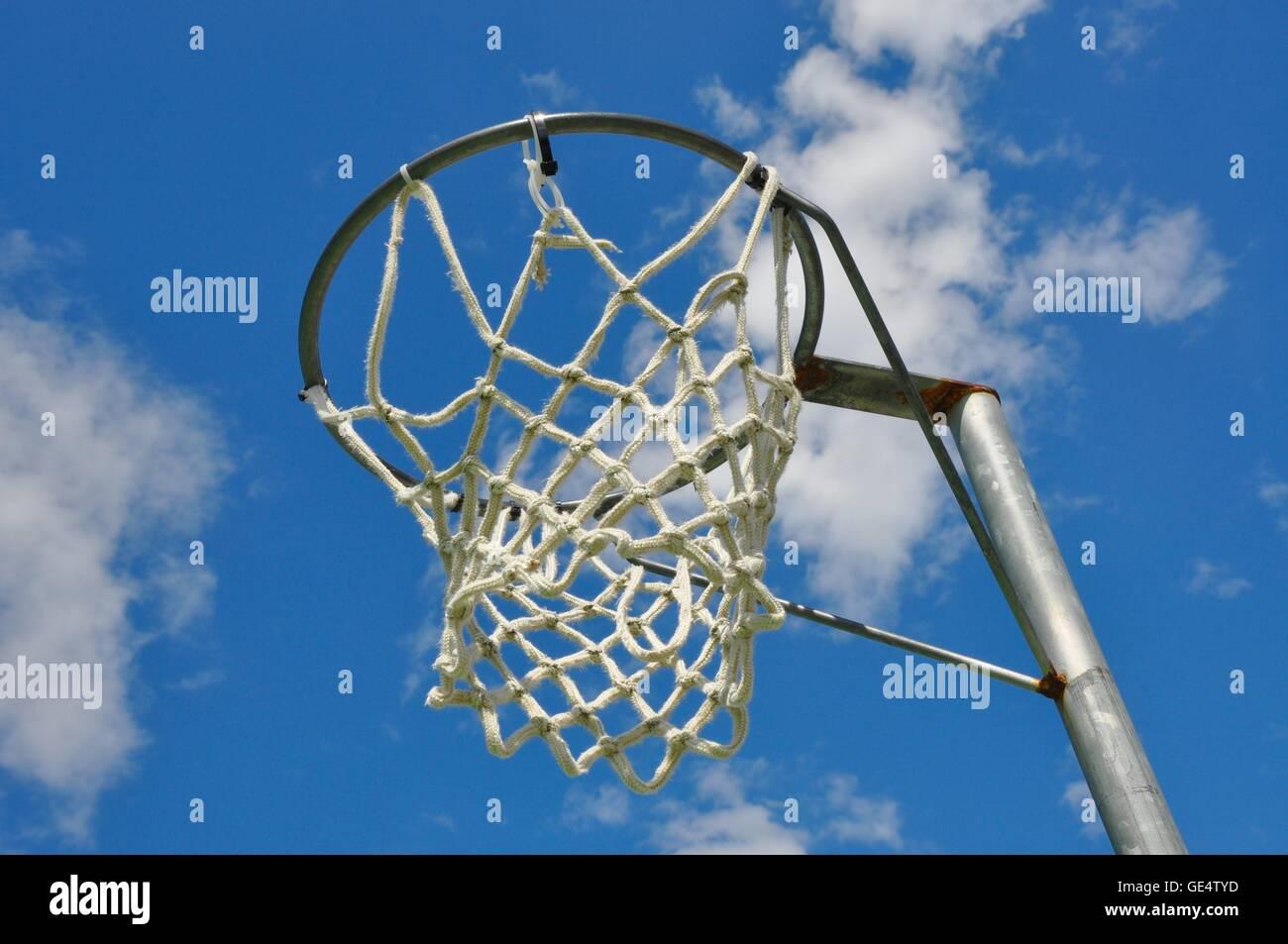 Perspective abstraite d'une jante de netball avec net contre un ciel bleu et fond de nuage. Photo Stock